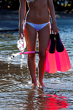 Healthy, fit female heads out to snorkel at Olowalu, Maui, Hawaii