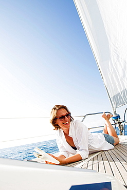 Smiling woman laying on boat