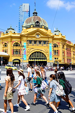 Pedestrians crossing street in front of historic Flinders Railway Station in central Melbourne Australia.