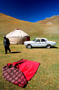 Old Russian car and yurt, Tash Rabat, Kyrgyzstan, Central Asia.