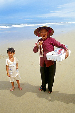 Hoi An, Beach, old Woman with a little Child, selling necklets, Traditional Costume, Woman wearing traditional conical Hat, Vietnam.