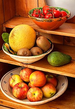 Assorted fruit and vegetables on a kitchen dresser.