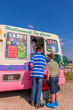 Walberswick, Suffolk, UK. 6th May 2013. Two boys enjoy the sunny weather on Bank Holiday Monday 6th of May 2013 as they buy ice creams at Walberswick, Suffolk, England, Britain, Uk.