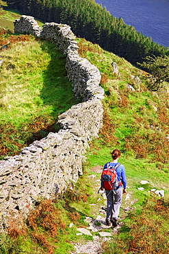 A female hiker walking down towards The Rigg at Haweswater in the Lake District.