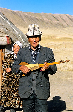 Kyrgyz Life, Nomad, a man is playing on a self made Guitar, in the backgroud his wife, Kyrgyzstan.