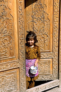 Osh, Kyrgyzstan, a Little Girl is looking out of her Door.
