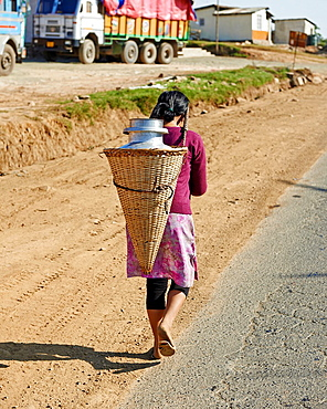 A young female labor worker carries rocks from the local quarry.