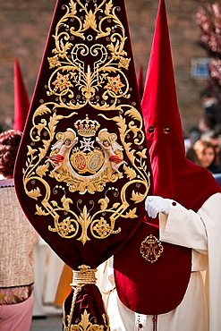 Detail penitent holding a banner with the coat of arms of the brotherhood during Holy Week, andalusia, Spain.