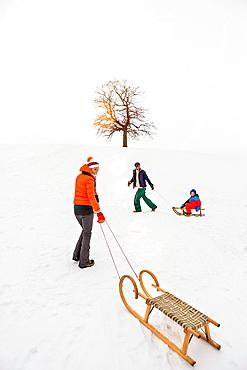 Woman pulling toboggan in snow