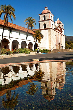 The Old Mission in Santa Barbara California is reflected in a fountain's pool of water.