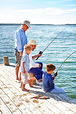 Boys with father and grandfather fishing, Utvalnas, Sweden