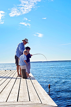Grandfather and grandsons fishing, Utvalnas, Sweden
