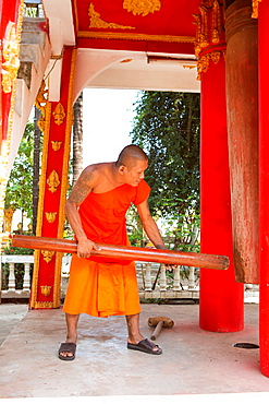 Monk hits huge wooden gong in Pha That Luang Temple in Vientaine, Laos.
