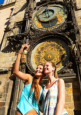 Prague. Czech Republic. Two young women taking picture in front of the Astronomical Clock with a smart phone.