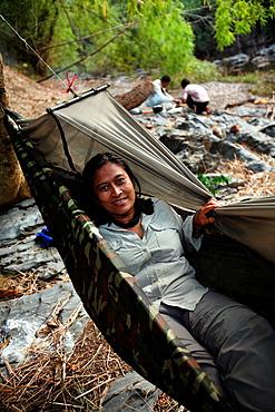 Tourists sleeping in hammocks along the O Chbar river. Dey Ei Trek, Mondulkiri, Cambodia.