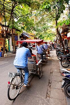 riding cyclos in Hanoi, Vietnam.