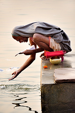 India, Uttar Pradesh, Varanasi, Hindu devotee in prayer.