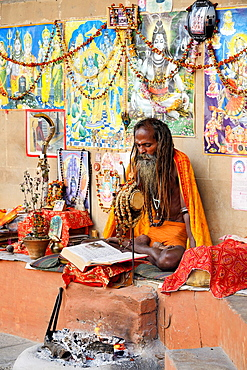India, Uttar Pradesh, Varanasi, Shivaite sadhu reading sacred texts.