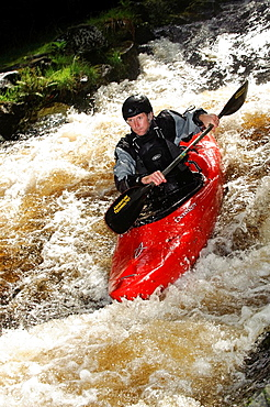 A person kayaking on the Trwyeryn river, National White Water Centre, canoeing watersports near Bala Gwynedd north wales UK