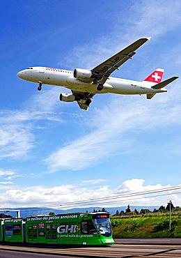 Swiss passenger jet liner flying over tram in Geneva, Geneva, Switzerland, Europe