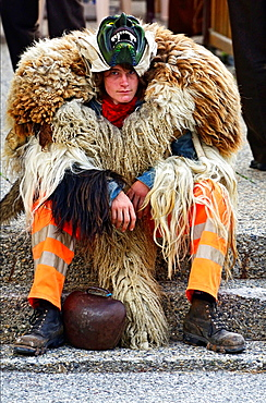 young man wearing traditional scaring Valasian mask of Tschaggatta, here resting for a moment because of heat, Nendaz, canton Valais, canton Wallis, Switzerland.