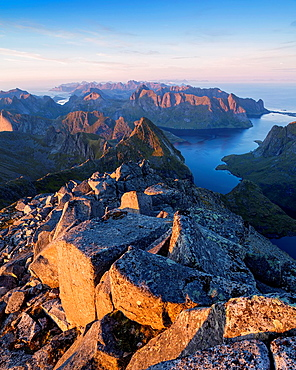Evening light over mountain landscape from rocky summit of Hermannsdalstinden, Moskenesoy, Lofoten Islands, Norway.