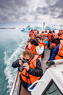 Taking pictures on a boat trip, Jokulsarlon Glacial Lagoon, Breidamerkurjokull, Vatnajokull Ice Cap, Iceland.