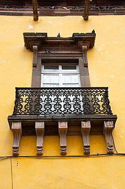 Colonial balcony. View on a typical urban scene with closed French window. San Miguel de Allende, Mexico.