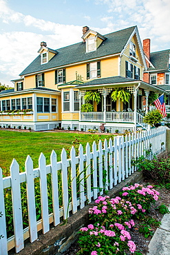 Cape May is America¥s first seaside resort. It has the largest collection of Victorian Architecture in the United States. A white picket fence, american flag and a flower bed is distinctly a nostalgic image of early 20th Century small town America
