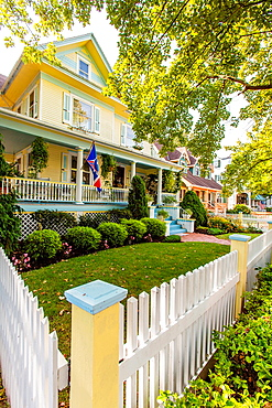 Cape May is America¥s first seaside resort. It has the largest collection of Victorian Architecture in the United States. A white picket fence, american flag and a front porch is distinctly a nostalgic image of early 20th Century small town America.