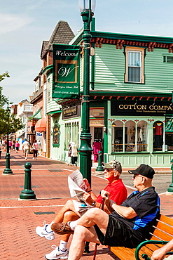 Pedestrian Mall in downtown Cape May, with two mature adults sitting on bench reading a paper.
