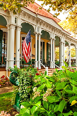 Cape May is America¥s first seaside resort. It has the largest collection of Victorian Architecture in the United States. A white victorian trim and an american flag and a front porch is distinctly a nostalgic image of early 20th Century small town America.