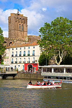Fortified Ancienne cathedrale St Etienne, 12thc., built in black lava,and river banks with restaurants along Herault river, and jousters training, AGDE town, Haut Languedoc,34 France.
