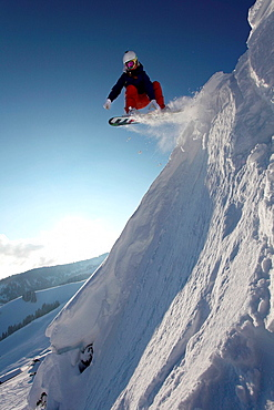 Snowboarder jumping down mountain