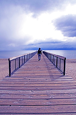 Young man in distance on jetty, Lake Tahoe, Nevada, USA