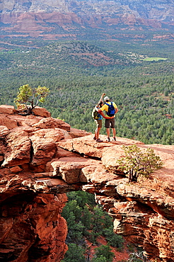 Hiking couple viewing from arched rock formation, Sedona, Arizona, USA