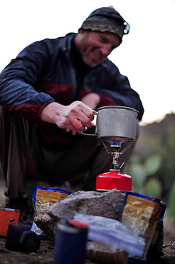 Backpacker preparing food on camping stove, Superstition mountains, Arizona, USA