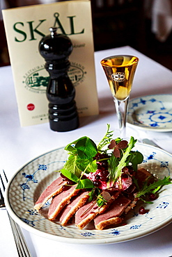 Smorrebrod, a Danish open sandwich of boiled salted duck with lingoberries cream and raw pickled cranberries with a glas of snaps, served at Restaurant Schonnemann Serving traditional Danish food, Copenhagen, Denmark.