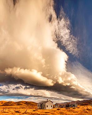 Dawn lights up cloudscape over historic (1939) farm buildings near St Bathans, Central Otago, New Zealand.