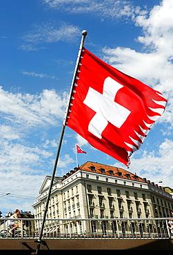 Swiss flag on Mont Blanc bridge, Geneva, Switzerland, Four Seasons Hotel des Bergues Geneva in the background