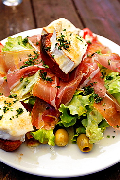 Salad with Goat Cheese and Prosciutto on Chavonnes lakeside restaurant. Villars, Vaud, Switzerland, Europe.