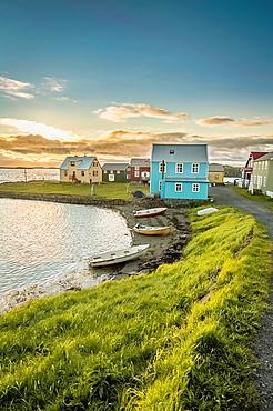 Homes and boats on the coastline of Flatey Island, Iceland.