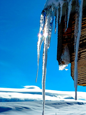 sun reflects in icicles at roof of cabine, Flaine, France