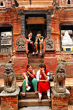 Young people sitting at Hindu temple, Durbar Square, Patan, Nepal