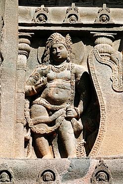 Cave 19 : Facade. Huge guardian figure on viewer's left of the chaitya arch. Ajanta Caves, Aurangabad, Maharashtra, India.