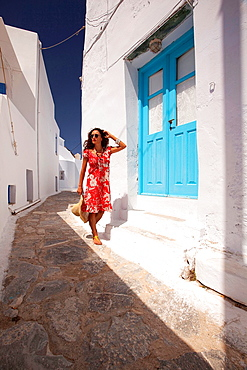 Tourist woman walking through the alley, Amorgos, Cyclades Islands, Greek Islands, Greece, Europe.