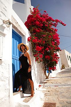 Woman posing in front of a house door, Amorgos, Cyclades Islands, Greek Islands, Greece, Europe.