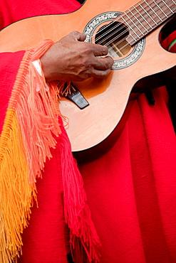 Indigenous man playing guitar, Cusco, Peru, South America.