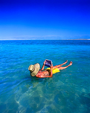 Floating man reading hebrew newspaper, Ein bokek, Dead sea, Israel.