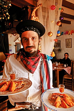 Waiter of Restaurante Bandolero, with the famed roasted pig, at Juzcar, Malaga province, Andalucia, Spain.